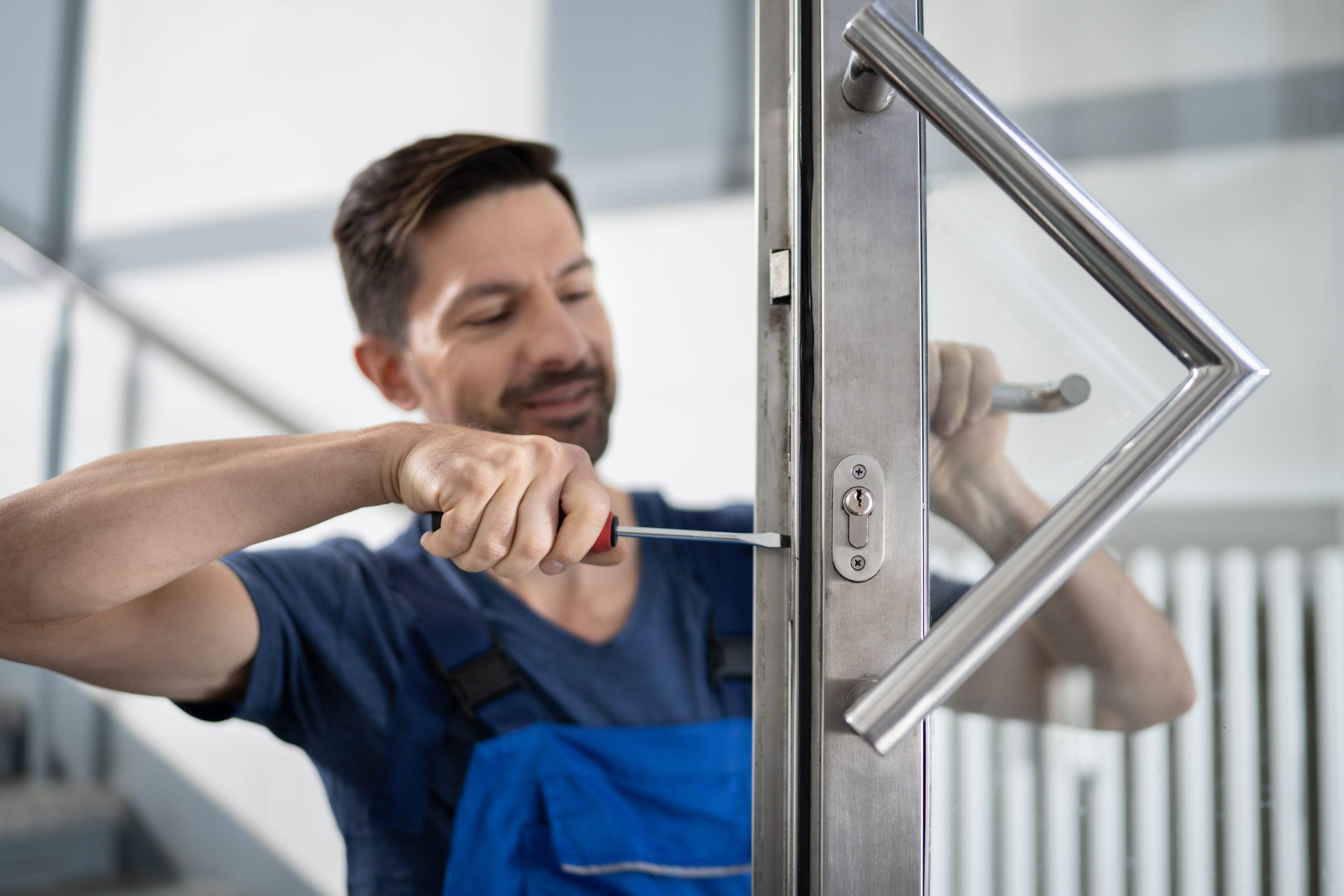 Serrurier réparant une porte vitrée
